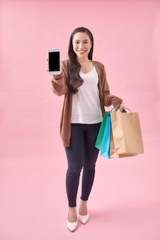 Foto de uma mulher bonita segurando sacolas de compras, mostrando a tela do celular em branco, sobre fundo rosa
