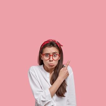 Foto de uma mulher caucasiana chateada com uma expressão facial descontente aponta no canto superior direito, franze o lábio inferior, usa óculos, descontente com os preços altos