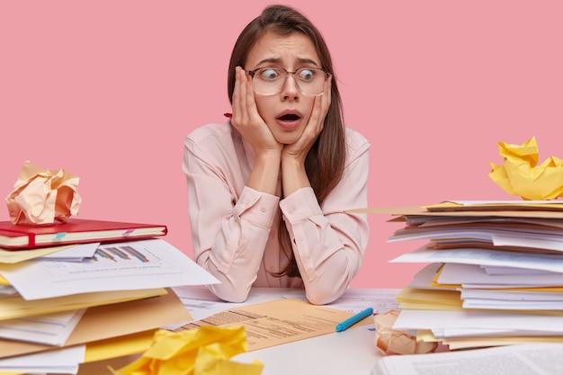 Foto de uma mulher caucasiana frustrada com cabelo escuro mantém as mãos no rosto, olha perplexa para uma pilha de documentos comerciais, não tem experiência em preparar um contrato