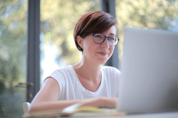 Foto de uma mulher com óculos trabalhando em seu laptop