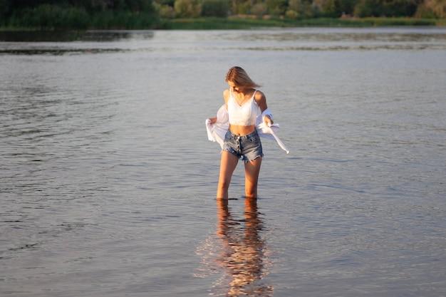 Foto de uma mulher com roupas brancas no fundo de um rio, uma bela jovem loira olhando para t ...