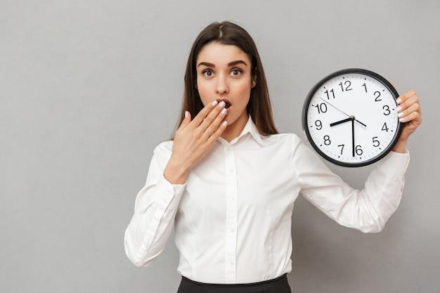 Foto de uma mulher confusa de escritório, de camisa branca e saia preta, segurando um grande relógio redondo e preocupada com o tempo, isolada sobre uma parede cinza
