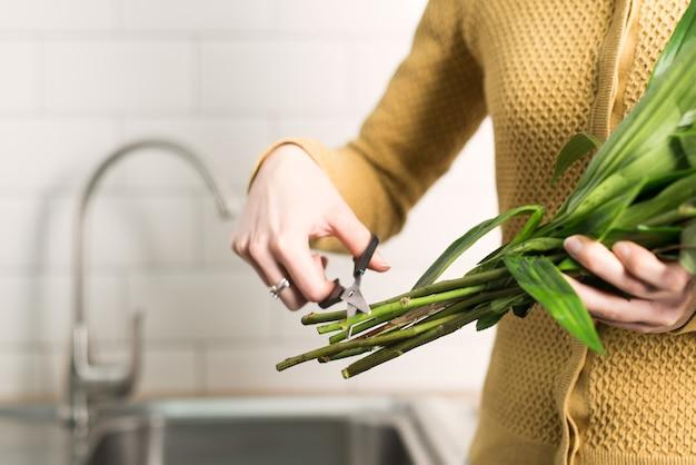 Foto de uma mulher cortando as pontas longas das flores com uma tesoura