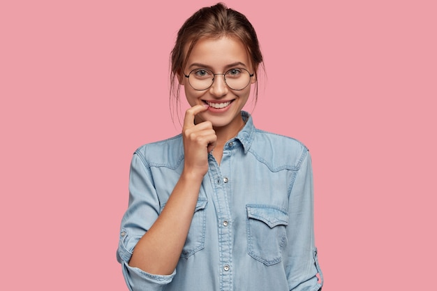 Foto de uma mulher de aparência agradável e amigável mantendo o dedo indicador perto da boca, sorrindo positivamente