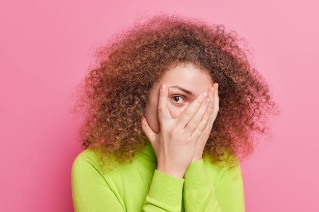 Foto de uma mulher de cabelo encaracolado espiando por entre os dedos. a expressão de medo cobre o rosto com as palmas das mãos tentando se esconder de alguém vestido com um macacão casual de manga comprida verde isolado na parede rosa