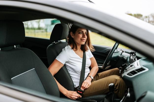 Foto de uma mulher de negócio que senta-se em um carro que põe sobre seu cinto de segurança.
