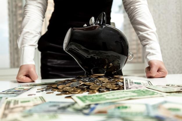 Foto de uma mulher de negócios em pé atrás do cofrinho na pilha de dinheiro