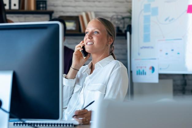 Foto de uma mulher de negócios inteligente falando no celular enquanto trabalhava com seu computador no escritório.