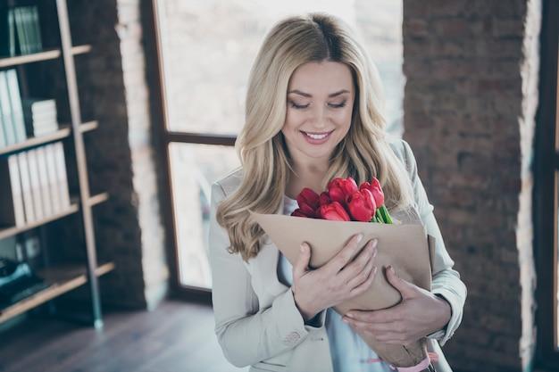 Foto de uma mulher de negócios segurando um buquê de tulipas frescas