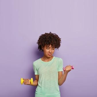 Foto de uma mulher de pele escura insatisfeita levanta halteres, faz exercícios, quer ser forte e saudável, vestida com uma camiseta casual, levanta peso