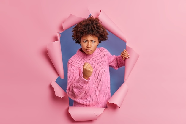 Foto de uma mulher de pele escura irritada com cabelo afro cerrando o punho demonstra raiva