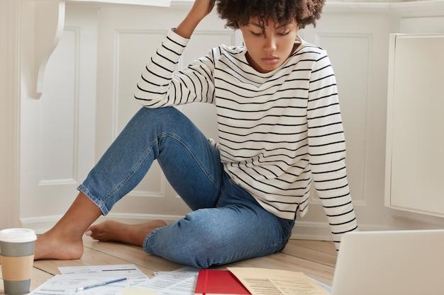 Foto de uma mulher de pele escura verifica os gráficos em papel durante um trabalho remoto, planeja a receita do orçamento