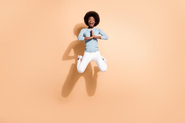 Foto de uma mulher de pele negra pulando de mãos dadas, gritando, isolada em um fundo de cor bege pastel