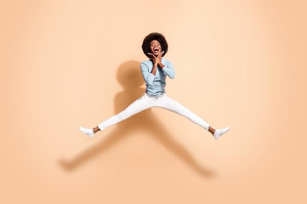 Foto de uma mulher de pele negra segurando as duas mãos perto do rosto, pulando com as pernas abertas, a boca aberta, isolada em um fundo de cor bege pastel