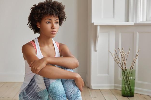Foto de uma mulher despreocupada e pensativa, com corte de cabelo afro, vestida com roupas esportivas e focada na distância