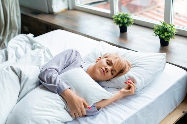Foto de uma mulher dormindo, deitada sob as cobertas e abraçando o travesseiro