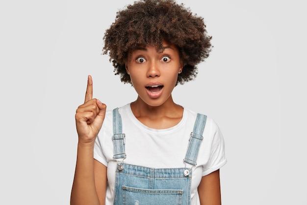 Foto de uma mulher emotiva de pele escura surpresa que prende a respiração, olha fixamente com olhos arregalados e levanta o dedo indicador