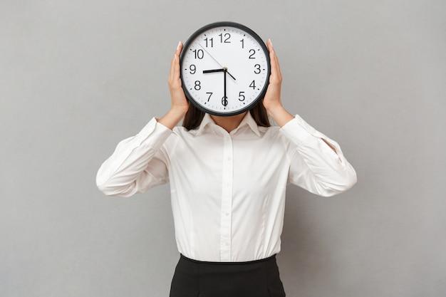 Foto de uma mulher engraçada em uma camisa branca e saia preta cobrindo o rosto com um grande relógio redondo, isolada sobre uma parede cinza