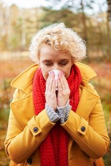 Foto de uma mulher espirrando com um lenço de papel nas mãos