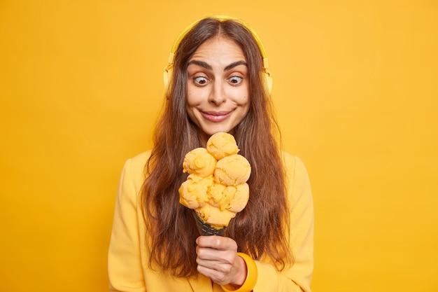 Foto de uma mulher europeia alegre e surpresa com cabelo escuro lg olhando para um sorvete apetitoso e morrendo de fome para comê-lo ouve música em poses de fones de ouvido sem fio estéreo em ambientes internos contra uma parede amarela