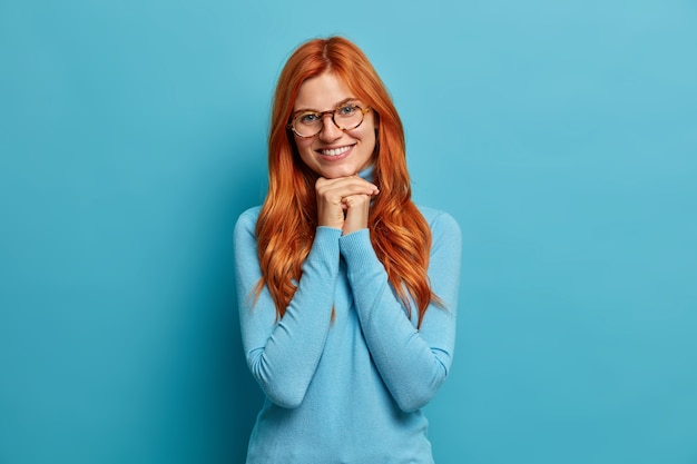 Foto de uma mulher europeia com cabelo vermelho mantém as mãos sob o queixo expressa emoções positivas usa óculos ópticos e gola olímpica casual.