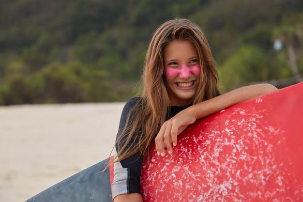 Foto de uma mulher européia de aparência agradável com expressão feliz, alegra-se com o dia por surfar, segura a prancha de surf encerada, gosta de esportes aquáticos, usa macacão, quer mostrar a curva inferior. tiro horizontal.