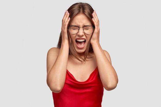 Foto de uma mulher europeia desesperada e estressante de mãos dadas na cabeça