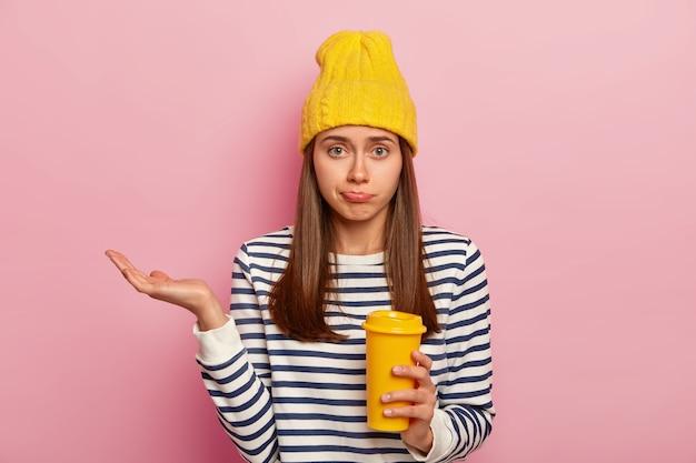 Foto de uma mulher europeia hesitante com expressão confusa, levanta a palma da mão, segura o café para viagem, usa um chapéu amarelo e um suéter listrado, posa sobre o fundo rosa.