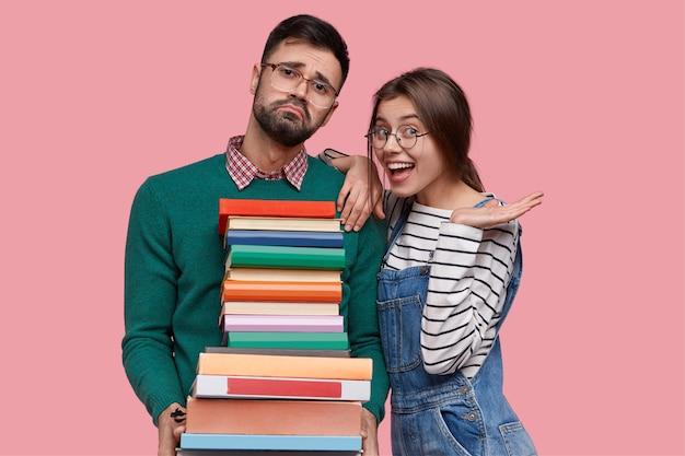Foto de uma mulher europeia positiva usando um macacão e suéter listrado, apoiada nos ombros de um nerd cansado com uma pilha de livros grossos