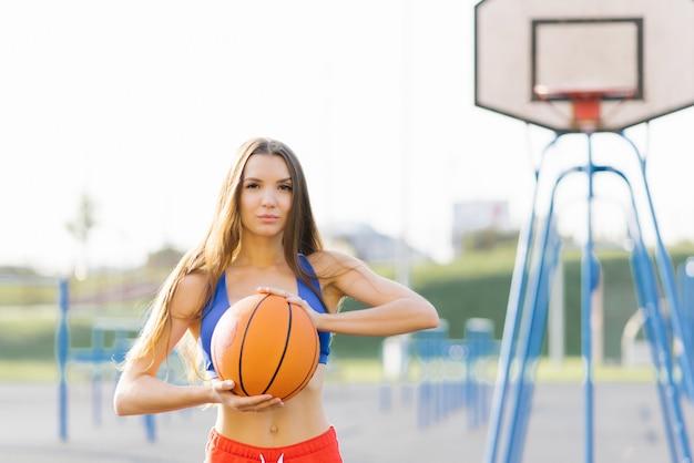 Foto de uma mulher europeia segurando uma bola de basquete durante um treino