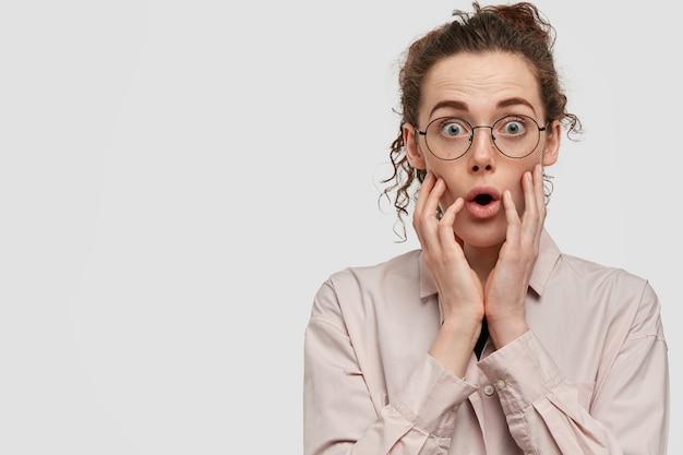 Foto de uma mulher européia surpresa com uma respiração ofegante em choque, arregala os olhos, usa uma camisa casual e fica encostada na parede branca