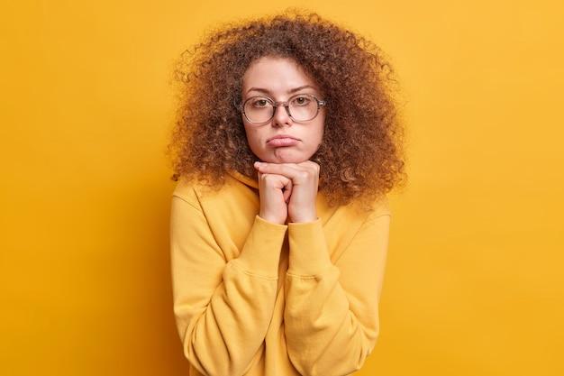 Foto de uma mulher europeia triste e decepcionada com cabelo encaracolado se sentindo chateada mantém as mãos embaixo do queixo franzindo os lábios vestindo um moletom isolado sobre a parede amarela se sentindo incômoda e entediada