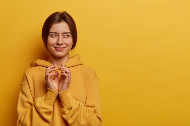 Foto de uma mulher feliz e misteriosa inclina os dedos e tem uma intenção misteriosa, trama alguma coisa, tem um olhar cunny de lado, usa um moletom, posa sobre a parede amarela, copie a área de espaço para seu texto.