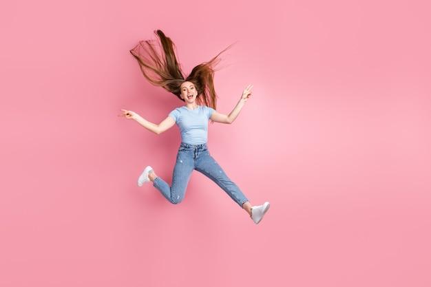 Foto de uma mulher gritando, mostrando dois sinais de v com os dedos pulando, isolados em um fundo de cor rosa pastel