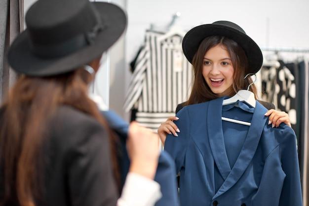 Foto de uma mulher jovem e atraente feliz sorrindo animadamente experimentando roupas novas em frente ao espelho no conceito de emoções de lazer de positividade de felicidade, estilo de vida, loja de roupas.