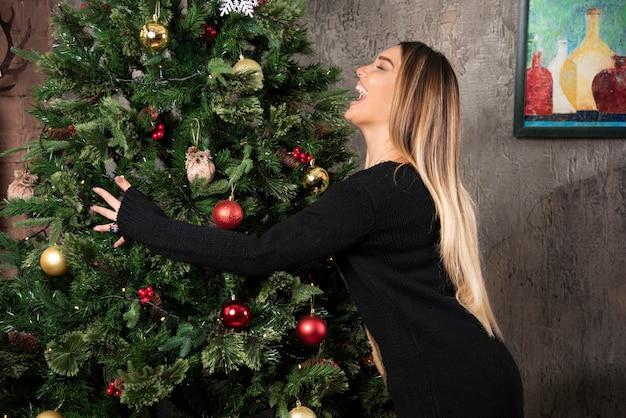 Foto de uma mulher loira abraçando a árvore de natal feliz