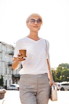 Foto de uma mulher loira adulta vestindo camiseta branca e óculos escuros, caminhando pelas ruas da cidade no verão e bebendo café para viagem em um copo de papel
