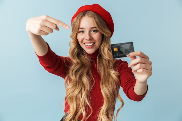 Foto de uma mulher loira atraente de 20 anos, usando boina vermelha, segurando o cartão de crédito isolado