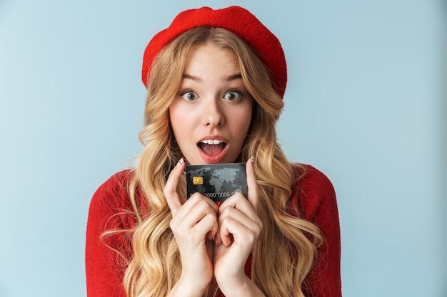 Foto de uma mulher loira de 20 anos usando uma boina vermelha segurando um cartão de crédito isolado