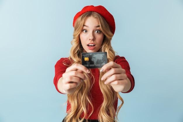 Foto de uma mulher loira de 20 anos usando uma boina vermelha, segurando um cartão de crédito isolado
