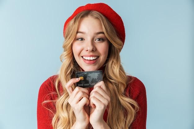 Foto de uma mulher loira encantadora de 20 anos usando boina vermelha segurando um cartão de crédito isolado