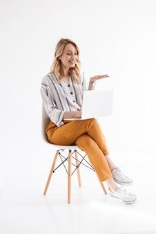 Foto de uma mulher loira europeia vestindo roupas casuais usando laptop e segurando copyspace enquanto está sentada em uma cadeira isolada sobre uma parede branca