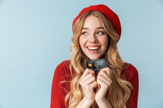Foto de uma mulher loira feliz de 20 anos, usando uma boina vermelha, segurando um cartão de crédito isolado