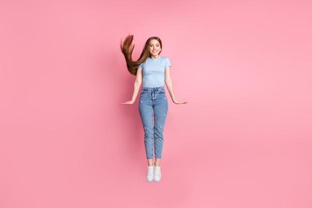 Foto de uma mulher modesta pulando isolada em um fundo de cor rosa pastel