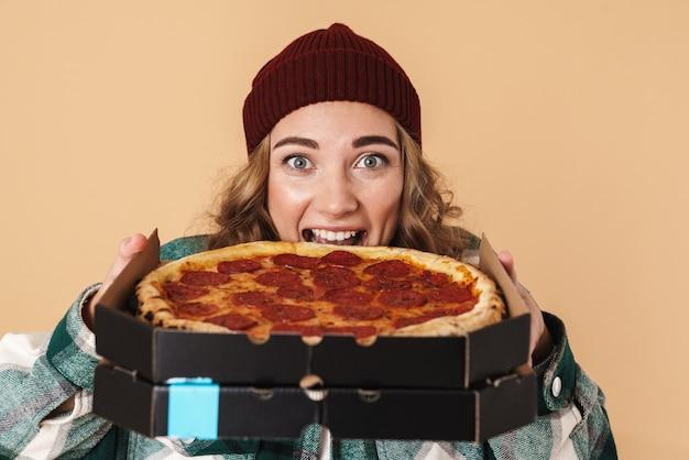 Foto de uma mulher muito animada com um chapéu de tricô comendo pizza isolada em bege