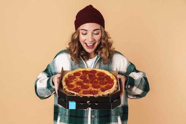 Foto de uma mulher muito satisfeita com um chapéu de malha segurando uma caixa com pizza e sorrindo isolada em bege