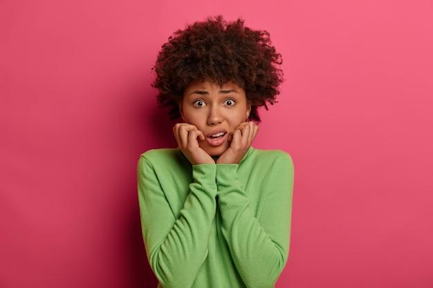 Foto de uma mulher nervosa preocupada que parece confusa, com medo de dizer algo, vestida com roupas casuais, isolada sobre uma parede rosa, tem expressão preocupada, sente medo. expressões faciais