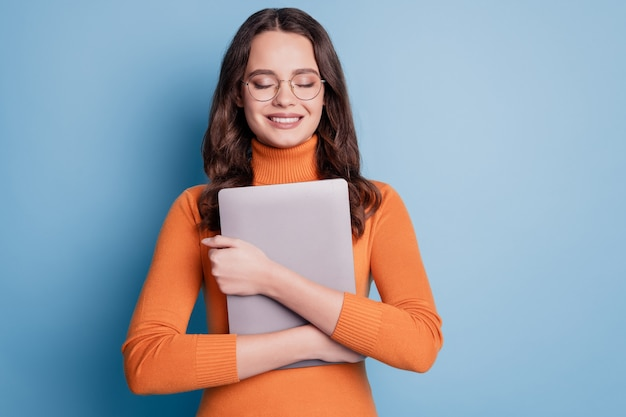 Foto de uma mulher pacífica com um abraço em um tablet de olhos fechados, um sonho posando em um fundo azul