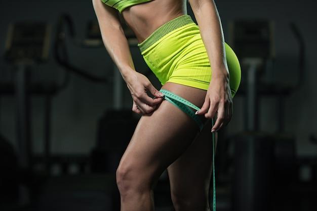 Foto de uma mulher que mede o tamanho do pé com uma fita métrica,