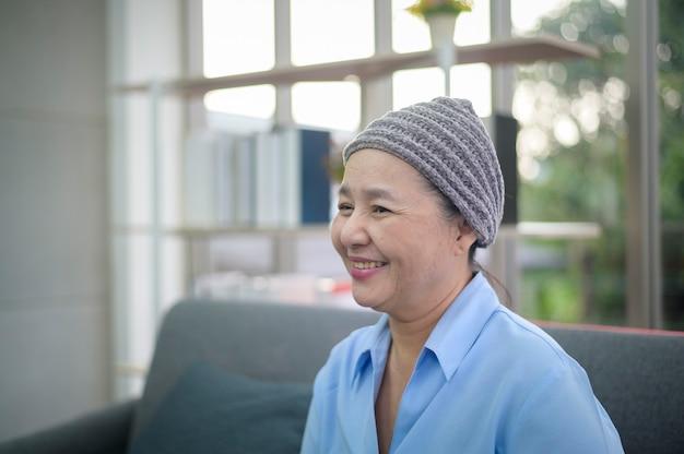 Foto de uma mulher sorridente com câncer em casa